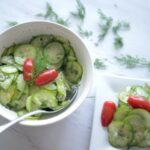 Cucumber Salad in a white bowl with spoon and on a square white plate