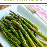Roasted Asparagus on a white plate with a fork and red & white strip napkin