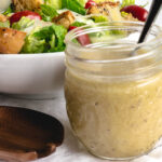 Caesar dressing in a glass jar with a white bowl of salad