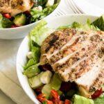 Sliced grilled chicken on a Greek salad