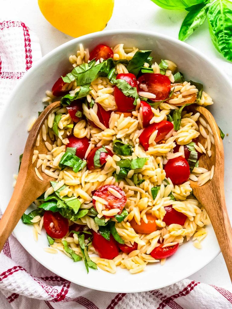 Finished orzo pasta salad with tongs in a bowl