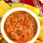 Salsa in a white bowl with chips surrounding it