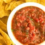 Offset white bowl with salsa in it and surrounded by chips