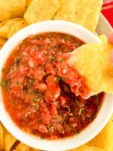 Salsa in white bowl chip in salsa