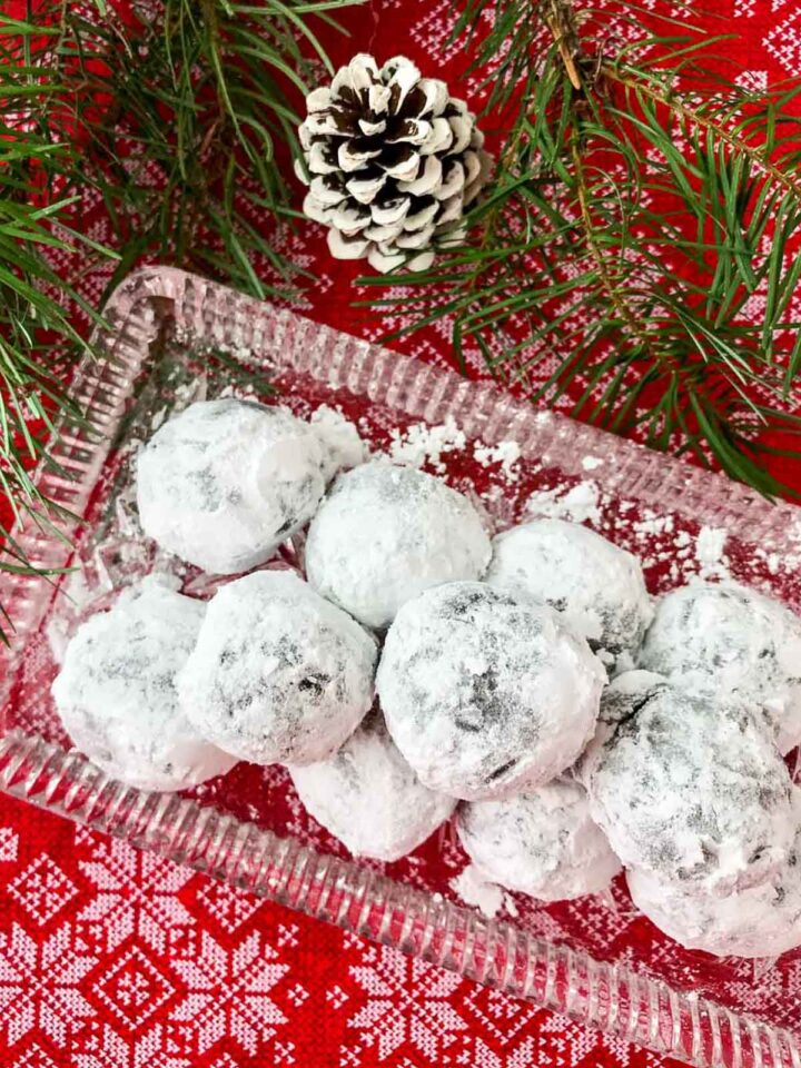 Rum balls on glass plate with white pine cone, pine tree branch