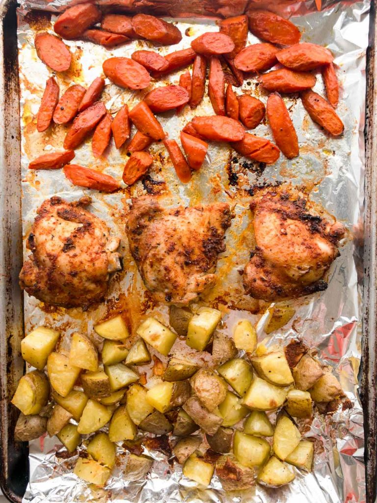 Baked sliced carrots, chicken thighs and potatoes on a sheet pan