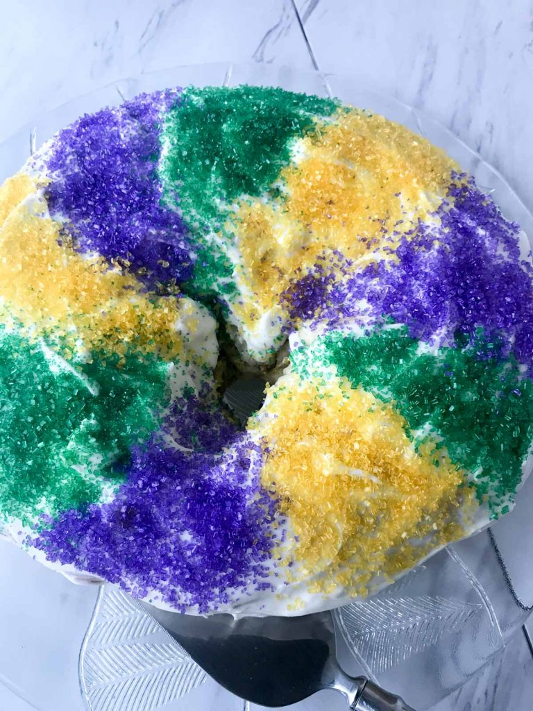 King cake with strips of green, yellow and purple sanding sugar