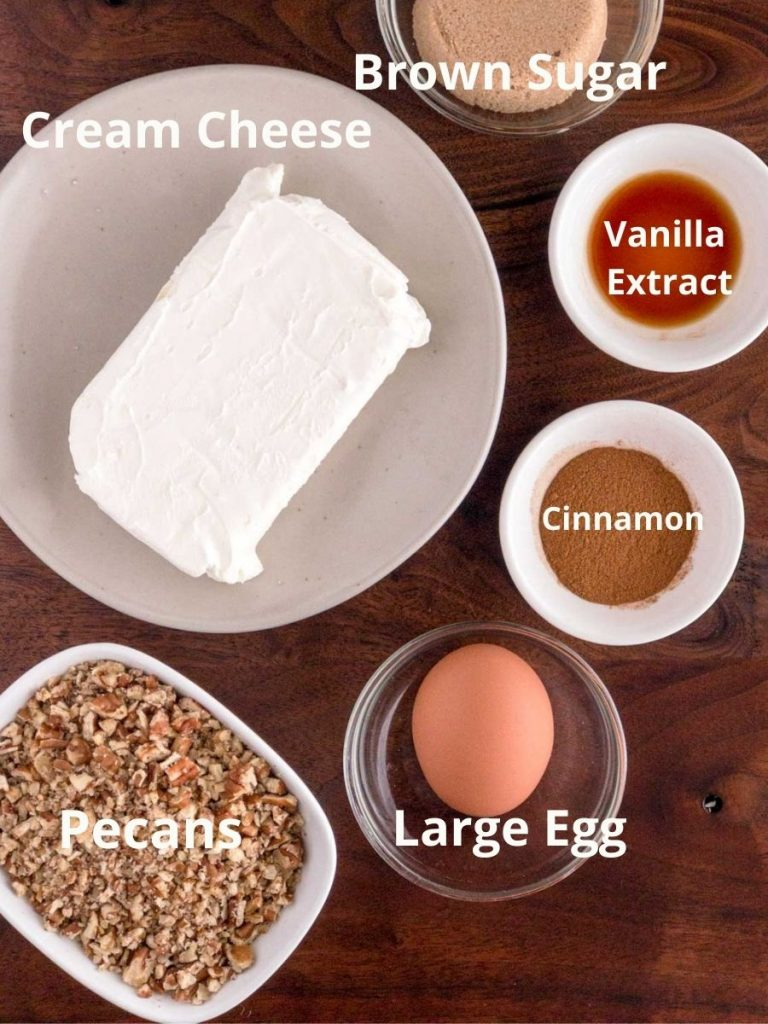 Cream cheese, Pecans, egg, cinnamon, vanilla in bowls on brown board