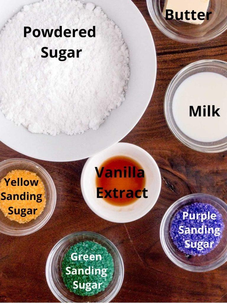 Powdered sugar, milk, vanilla extract, yellow sugar, green sugar and purple sugar in bowls on brown board