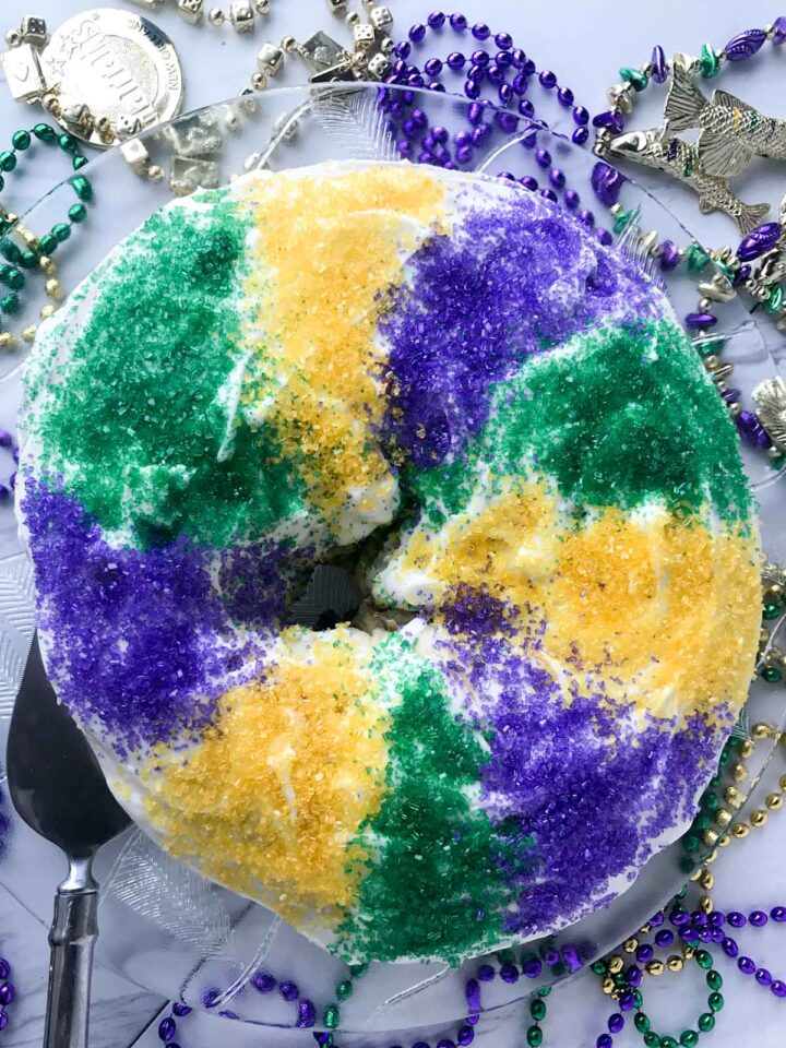 King cake with Mardi Gras beads surrounding it
