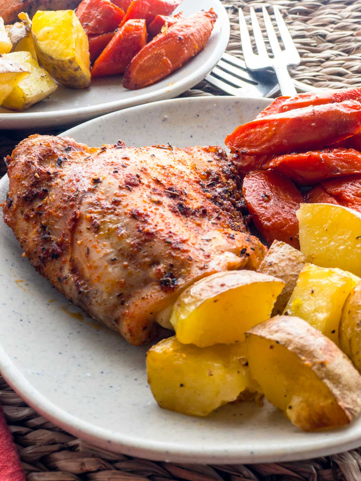 Spice baked chicken thigh with roasted carrots and potatoes on a plate