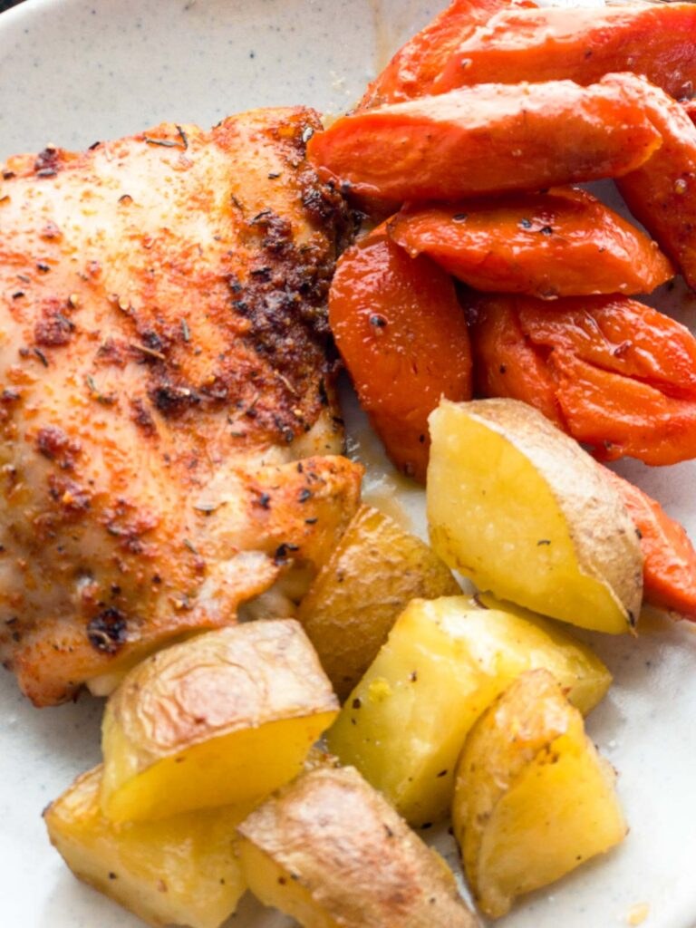 Roasted chicken, carrots and potatoes on a plate