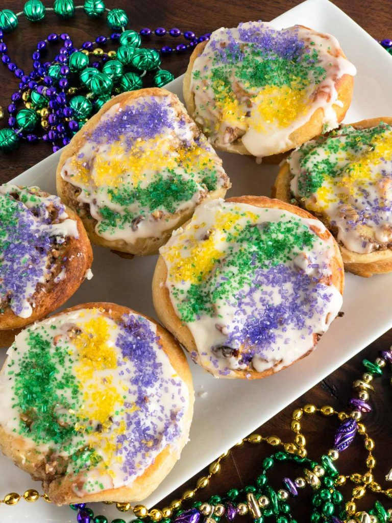 Miniature king cakes on a white plate with mardi gras beads in the background