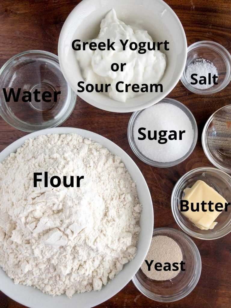 Flour, water, yogurt, sugar, salt, butter and yeast in bowls on a brown board