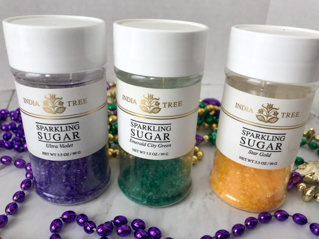 Purple, green and yellow sanding sugars in a plastic shaker