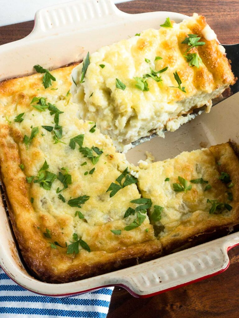 Baked egg and cheese casserole with parsley sprinkled on tp