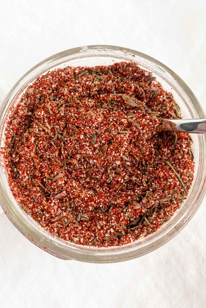 Top view of seasoning blend in a jar with spoon inserted in mix