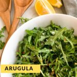 Arugula salad in a white bowl with brown salad tongs and a lemon on the side