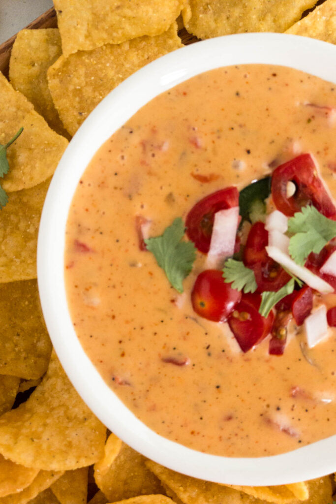 Queso in a white bowl garnished with diced tomatoes, onions and cilantro.  Tortilla chips surround the bowl