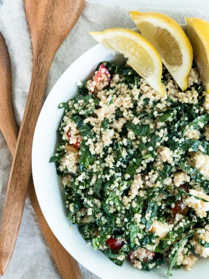 Kale and Quinoa salad in a white bowl with lemon wedge garnish