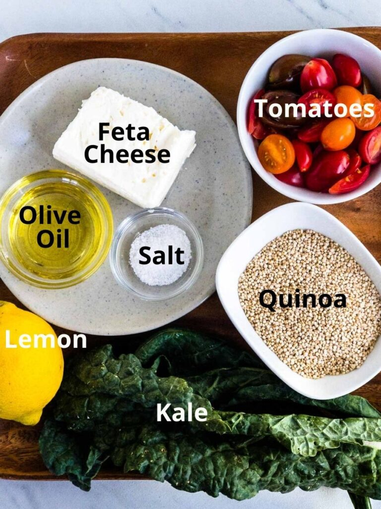 Lemon, Kale, Feta cheese, salt, olive oil, quinoa, tomatoes, in bowls on wood service