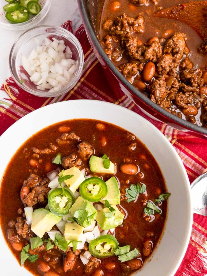 Turkey chili in a white bowl garnished with onions, avocado and jalapeno s