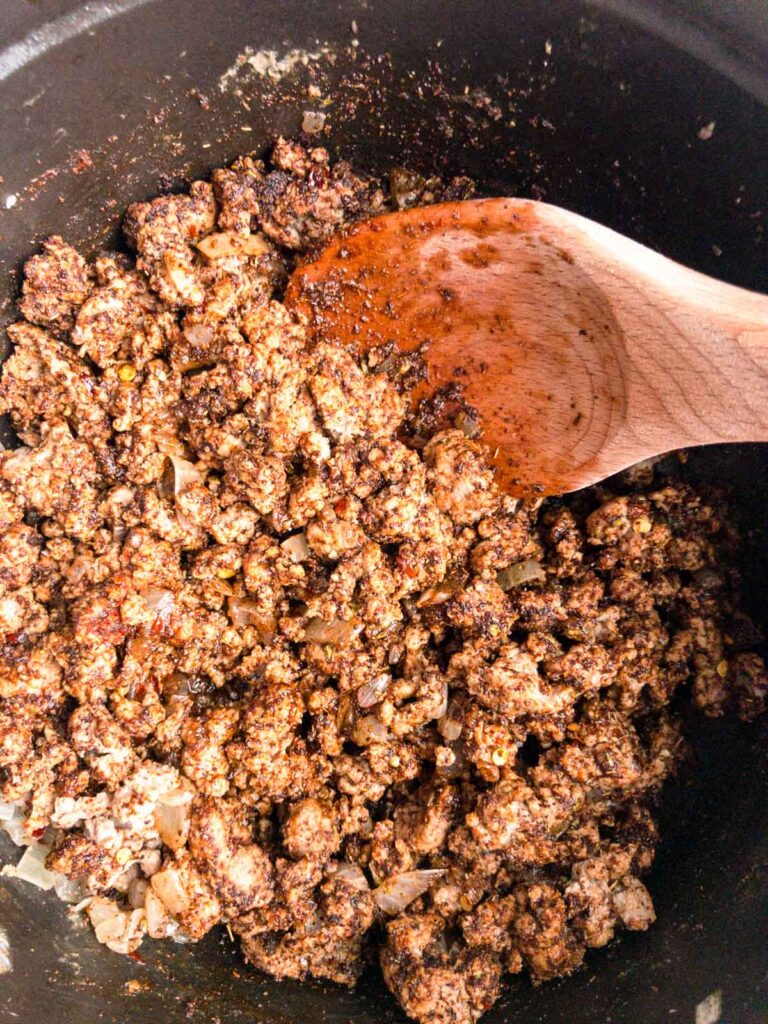 Chili seasonings cooking in turkey meat in a pot