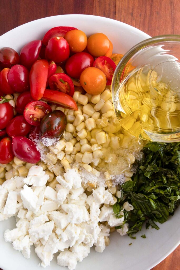 Adding oil to tomatoes, feta cheese, basil and corn