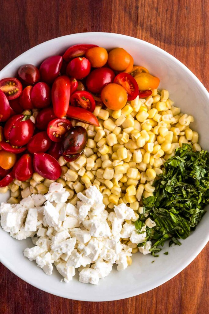 Sliced tomatoes, crumbled feta cheese, sliced basil on top of corn in a white bowl