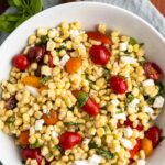 Corn, cherry tomatoes, feta cheese and sliced basil in a white bowl.