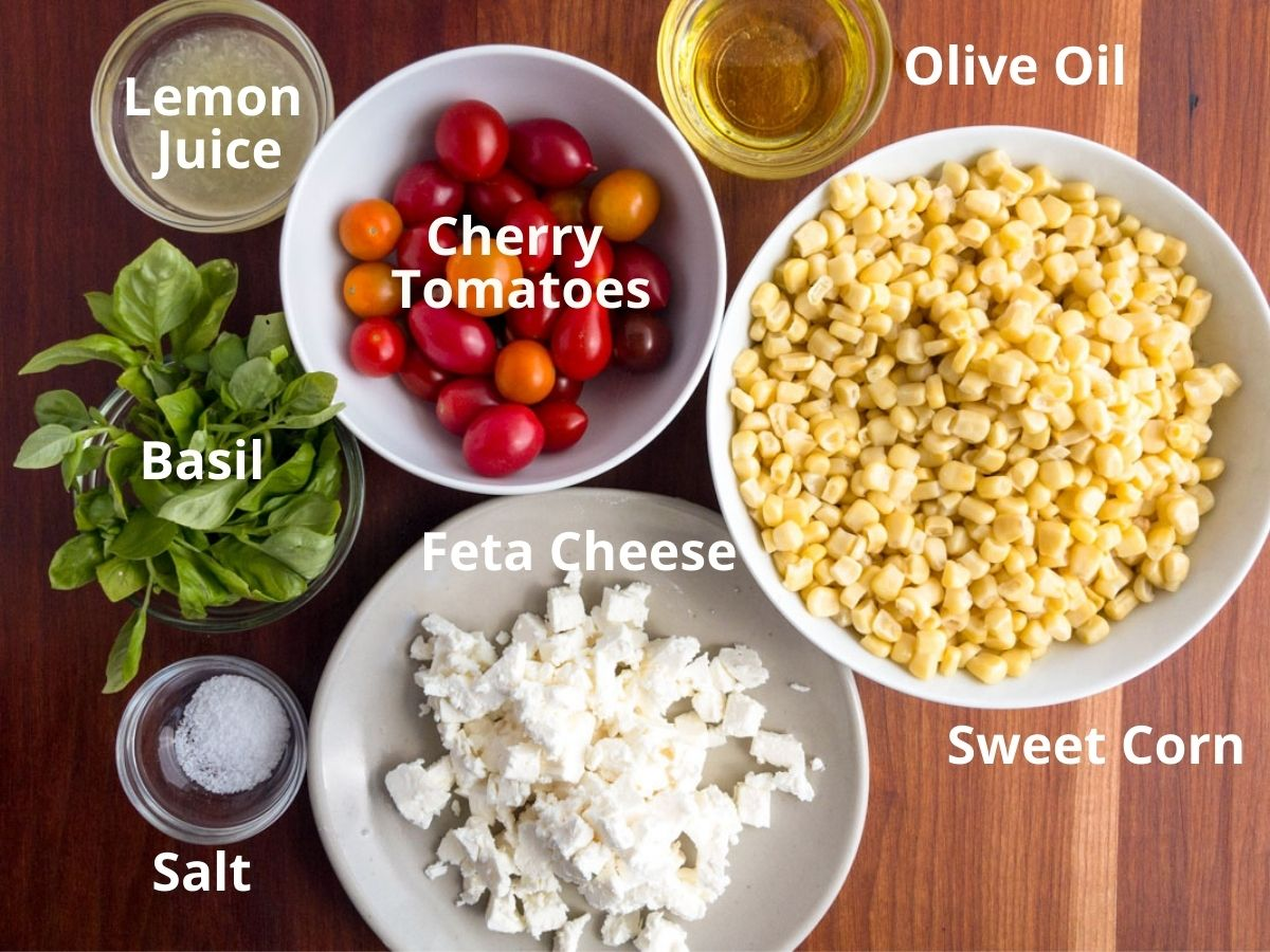 Corn, cherry tomatoes, feta cheese, salt, basil, lemon juice and oil in separate bowls on a wood board