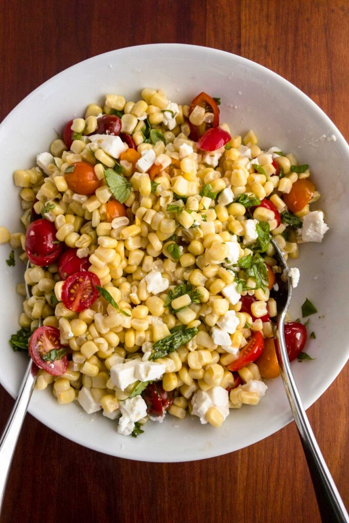 Tossing corn and tomato salad