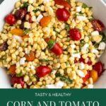 Corn, Tomato, feta cheese, basil salad in a white bowl